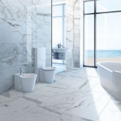 """Marble Attache in Calacatta 24"""" x 48"""" matte field tile on the floor and polished field tile on the wall."""